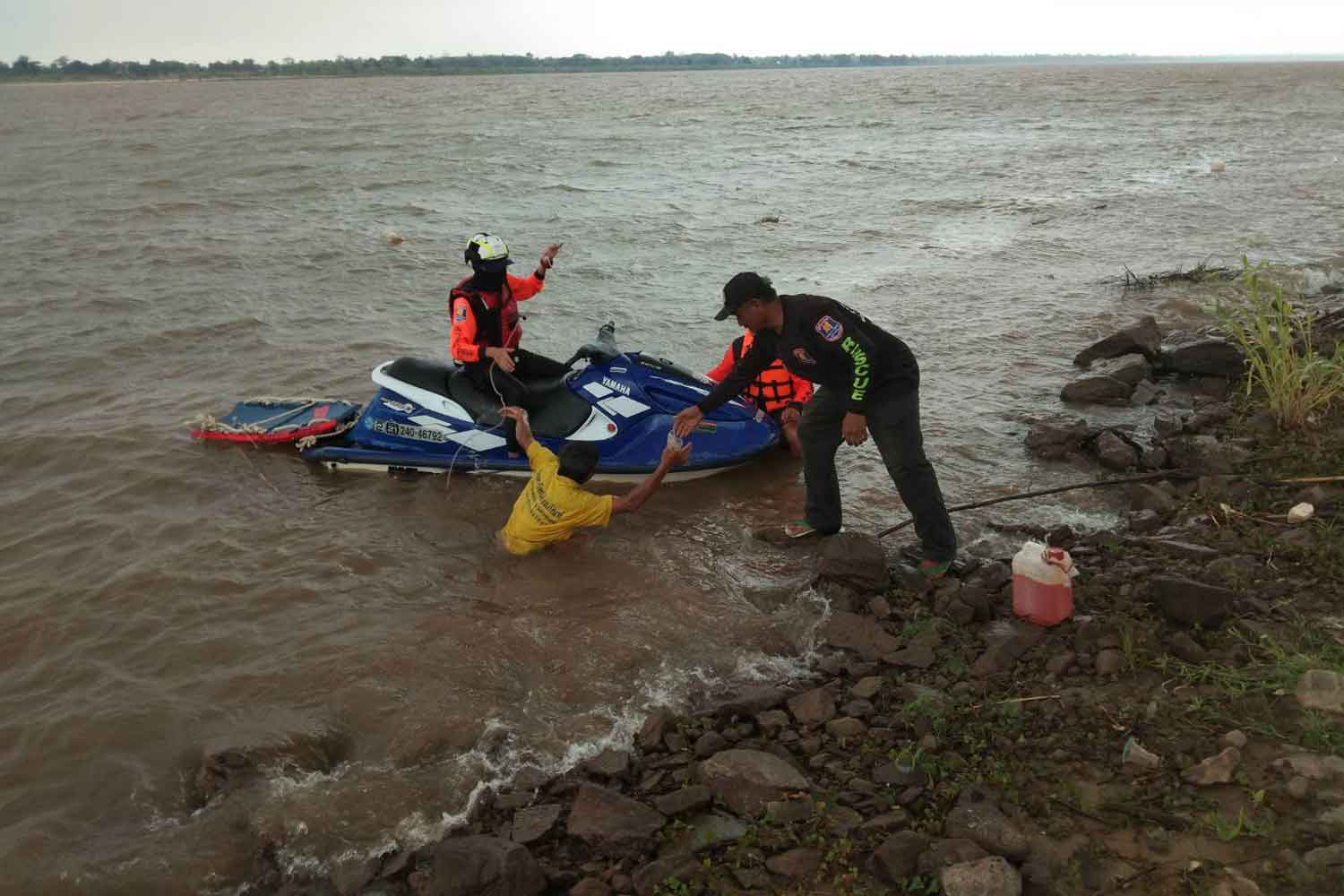A rescued fisherman is brought to the bank of the Mekong river in Nakhon Phanom's That Phanom district. Three small fishing boats capsized in the middle of river during a storm on Monday afternoon. One fishermen drowned. (Photo: Pattanapong Sripiachai)