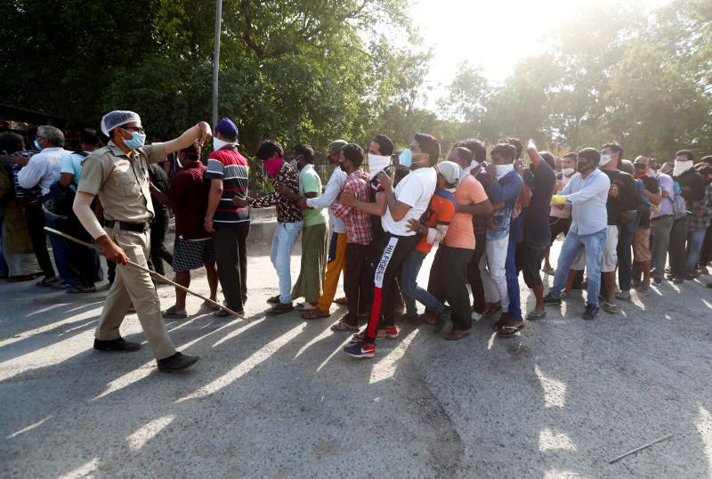 A police officer tries to control the crowds outside a wine store during an extended nationwide lockdown to slow down the spread of the coronavirus disease, in New Delhi, India on Monday. (Reuters photo)