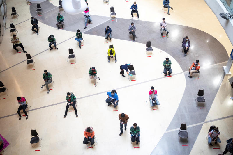 Staff of food delivery companies sit on social-distancing chairs due to the coronavirus disease outbreak, as they wait for customers' orders at a shopping mall in Bangkok April 10, 2020. (Reuters file photo)