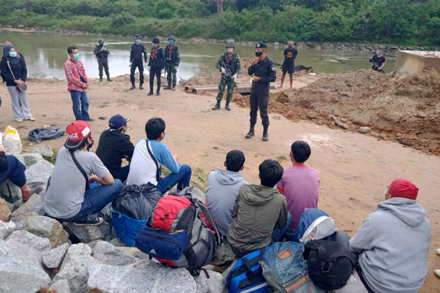 Security officers speak to Thai workers who illegally crossed the border back from Malaysia to Sungai Kolok district of Narathiwat late last month. Waedao Harai