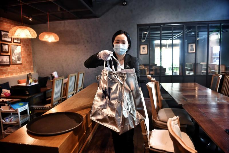 An employee from luxury food delivery service White Glove Delivery collects an order from high-end restaurant At-Ta-Rote for a client in Bangkok on Monday, with the company providing a premium experience for online food orders during the Covid-19 coronavirus pandemic. -(AFP photo)