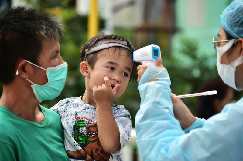 A young resident of the Klong Toey community has his temperature taken as he takes part in testing for the Covid-19 novel coronavirus in Bangkok on Wednesday. (AFP photo)