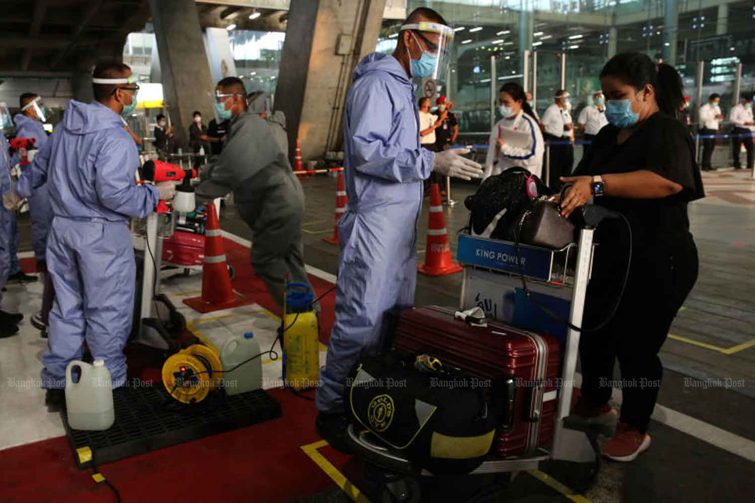 Officials sanitise the luggage of returnees at Suvarnabhumi airport in Samut Prakan province early this month. (Photo: Wichan Charoenkiatpakul)