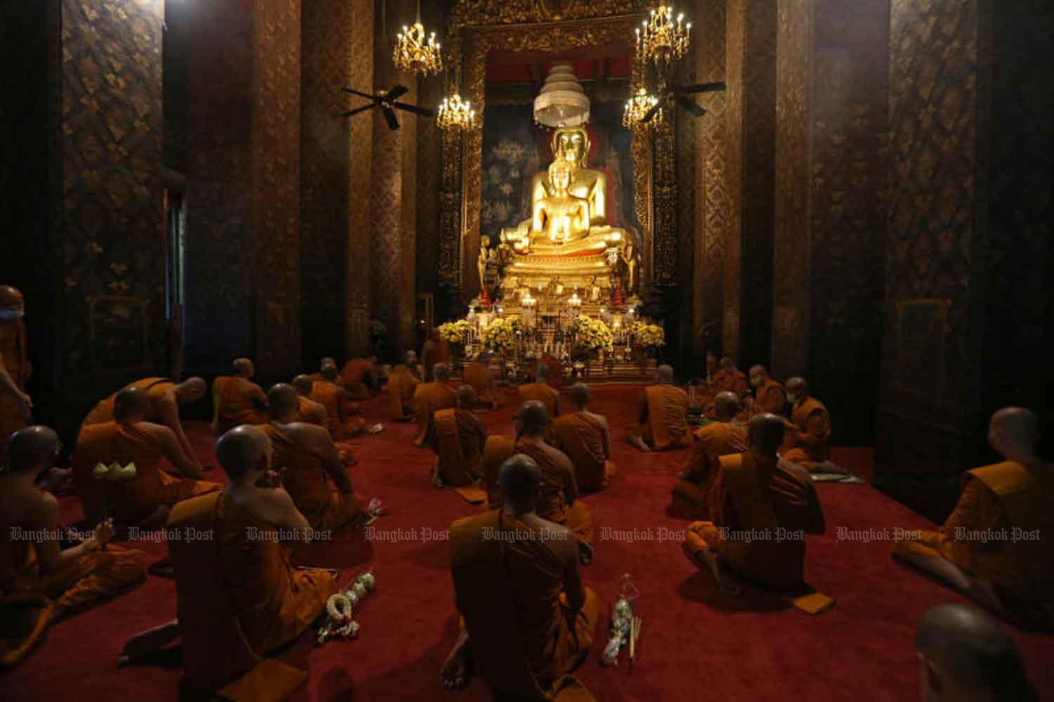 Monks at Wat Bowon Niwet in Bangkok prepare to conduct a prayer inside the temple's ubosot to mark Visakha Bucha Day on Wednesday night. The temple live-streamed the ceremony, including a candlelight vigil, so people could join the activity in their homes as part of measures to curb the spread of Covid-19. (Photo by Varuth Hirunyatheb)