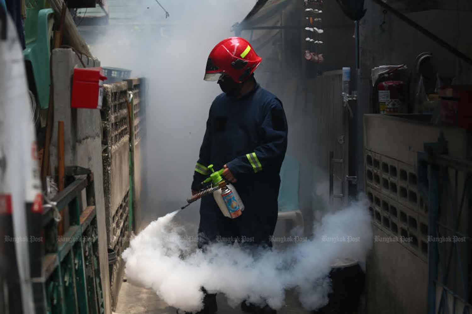 A volunteer sprays chemicals to kill mosquitos and virus at Wat Klong Toey Nai 2 community in Klong Toey district, Bangkok, on Thursday. (Photo by Varuth Hirunyatheb)