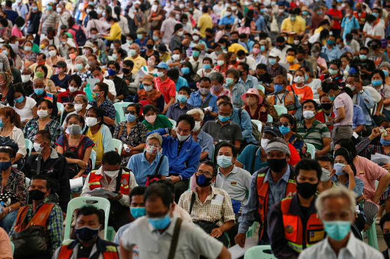 People wait for financial aid near the Finance Ministry office in Bangkok on Thursday. (Reuters photo)