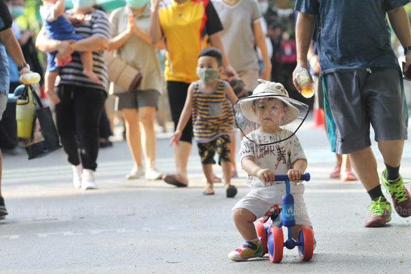 A boy wears a protective face shield during his visit to Suan Rod Fai. (Photo by  Nutthawat Wicheanbut)