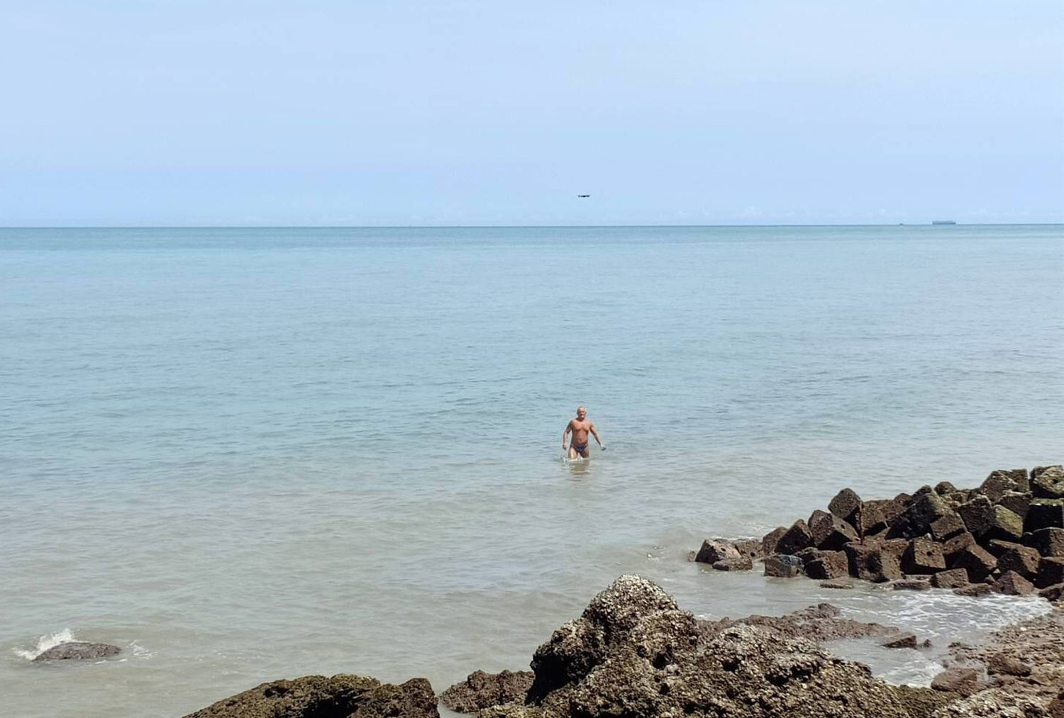 One of the three foreigners spotted swimming at a closed beach behind a hotel in Pattaya emerges from the water on Saturday. (Photo by Chaiyot Pupattanapong)