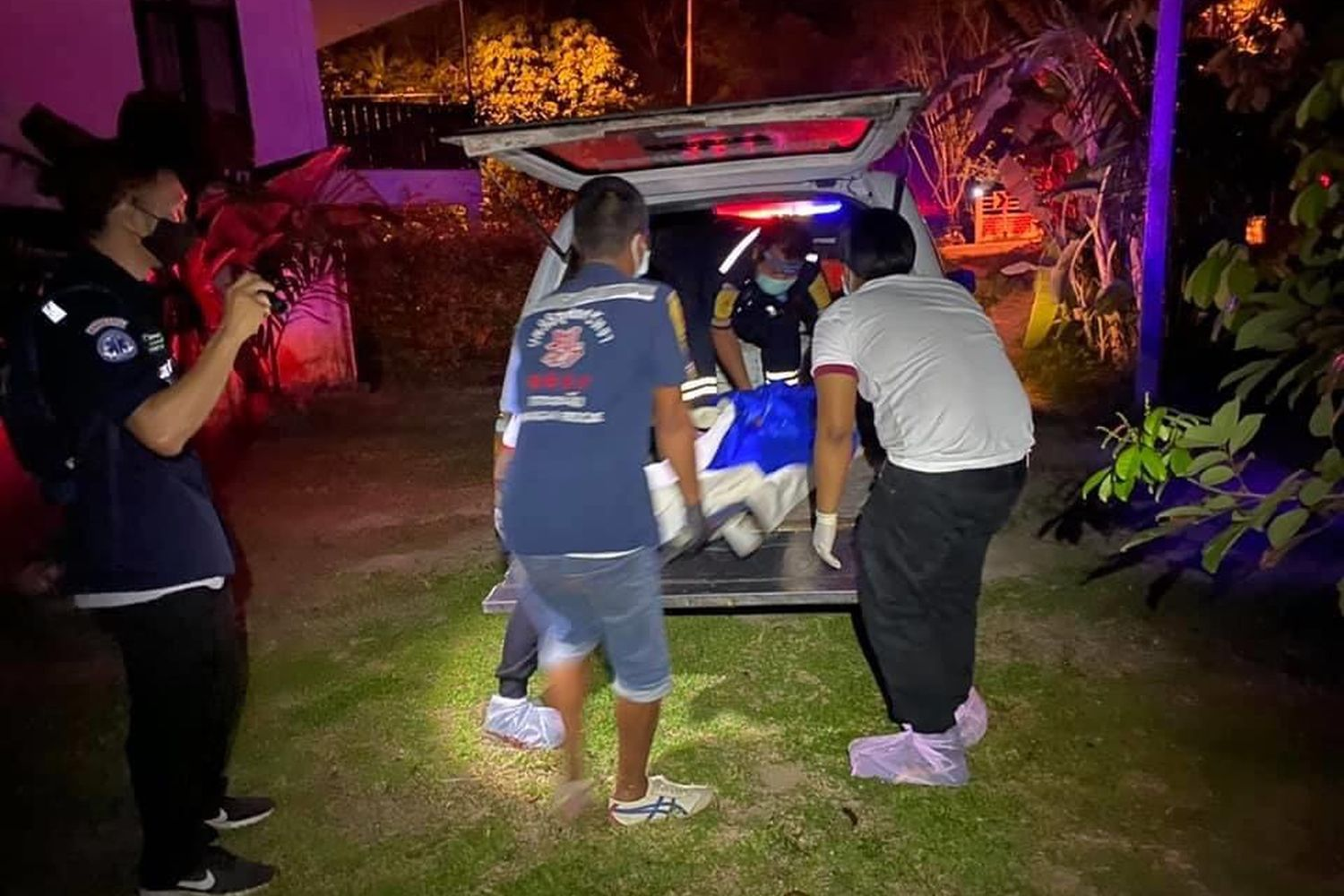 Rescue workers carry the body of the Chilean man who was stabbed to death at his house on Koh Phangan, Surat Thani, in the early hours of Saturday. (Photo supplied by Supapong Chaolan)