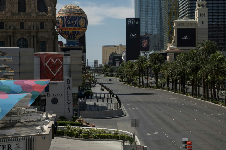 A car drives down the Las Vegas strip, which the pandemic has deprived of its drunken revelers and packed poker tables