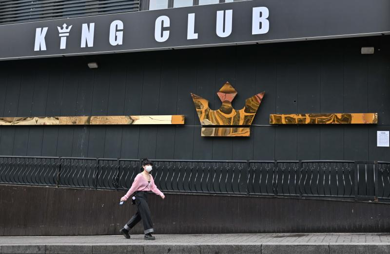 A woman wearing a face mask walks past a night club, now closed following a visit by a confirmed coronavirus patient, in the popular nightlife district of Itaewon in Seoul on Sunday. (AFP photo)