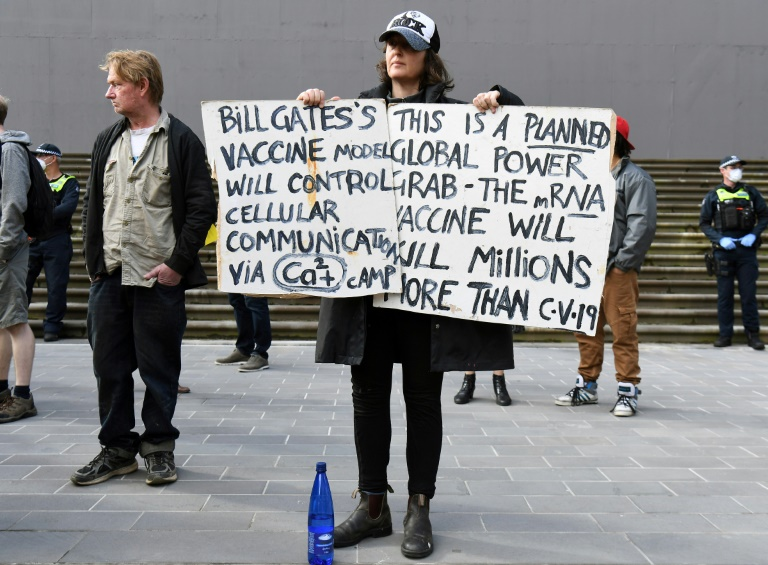 An anti-lockdown protester holds placards on the steps of Victoria's state parliament in Melbourne.