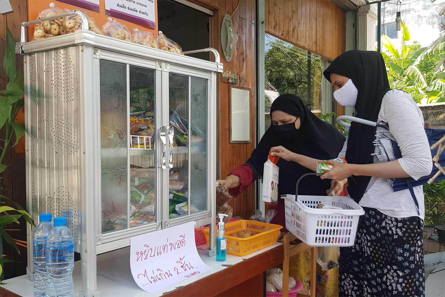 People place items in a community pantry in Muang district of Phitsanulok. The pantries have been found in 43 provinces as of Monday. (Photo by Chinnawat Singha)