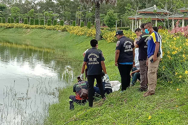 Rescue volunteers wrap the body of the baby in white cloth after he was retrieved from a park pond at Walailak University on Nakhon Si Thammarat on Monday. (Photo: Nujaree Raekrun)