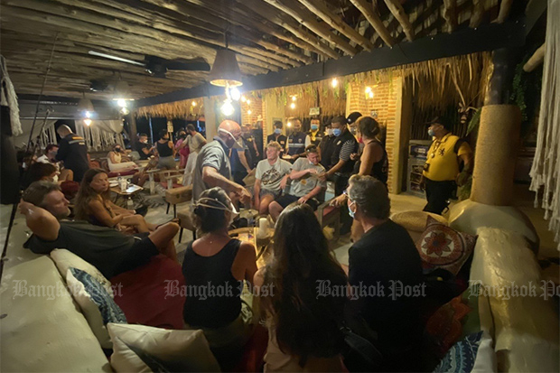 Police raid La Bohemia bar beer on Sunday night, and charge 22 foreigners and two Thais with violating the emergency decree, on Koh Samui in Surat Thani. (Photo: Supapong Chaolaen)