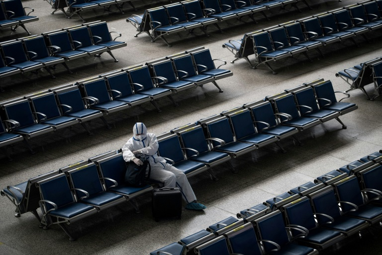 A passenger wears a hazmat suit as a precaution against the Covid-19 coronavirus as he waits for a train at Hankou Railway Station in Wuhan.