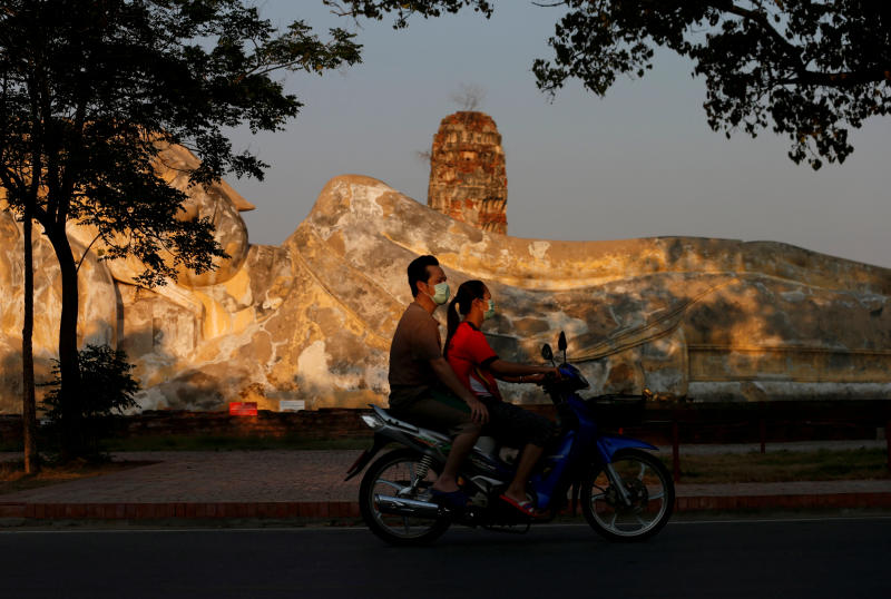 People ride a motorbike as they wear protective face masks amid the empty ancient temples usually crowded with tourists following the coronavirus disease outbreak, at the ancient city of Ayutthaya, March 30, 2020. (Reuters photo)