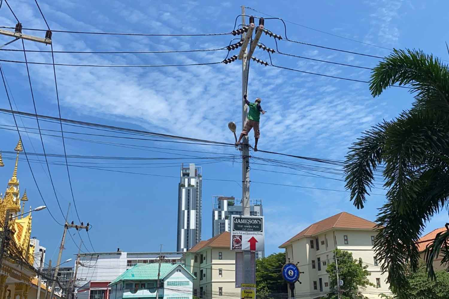 Paiboon Wisetsri, 59, complains loudly from a power pole in Pattaya, Chon Buri, on Tuesday morning. (Photo: Chaiyot Pupattanapong)