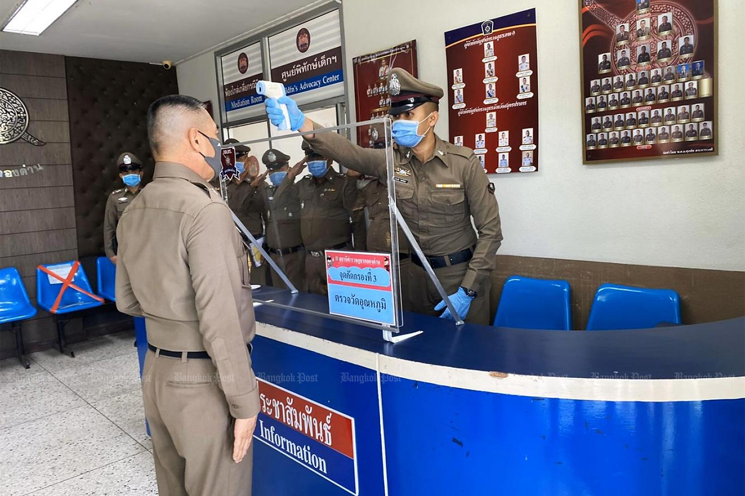 National police chief Chakthip Chaijinda has his temperature checked before entering Klong Dan police station where he asked about progress in the investigation into alleged extortion committed by some of the station's officers.(Photo by Atchariya Ruengrattanapong)