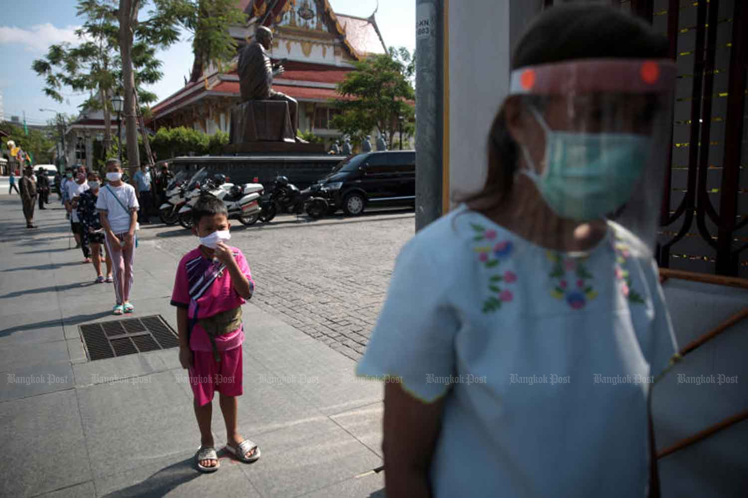 Safe distancing is the norm, as people queue to receive assistance packages at Wat Rakhang Khositaram in Bangkok on Wednesday morning, when the government announced there were no new Covid-19 cases over the previous 24 hours. (Photo: Chanat Katanyu)