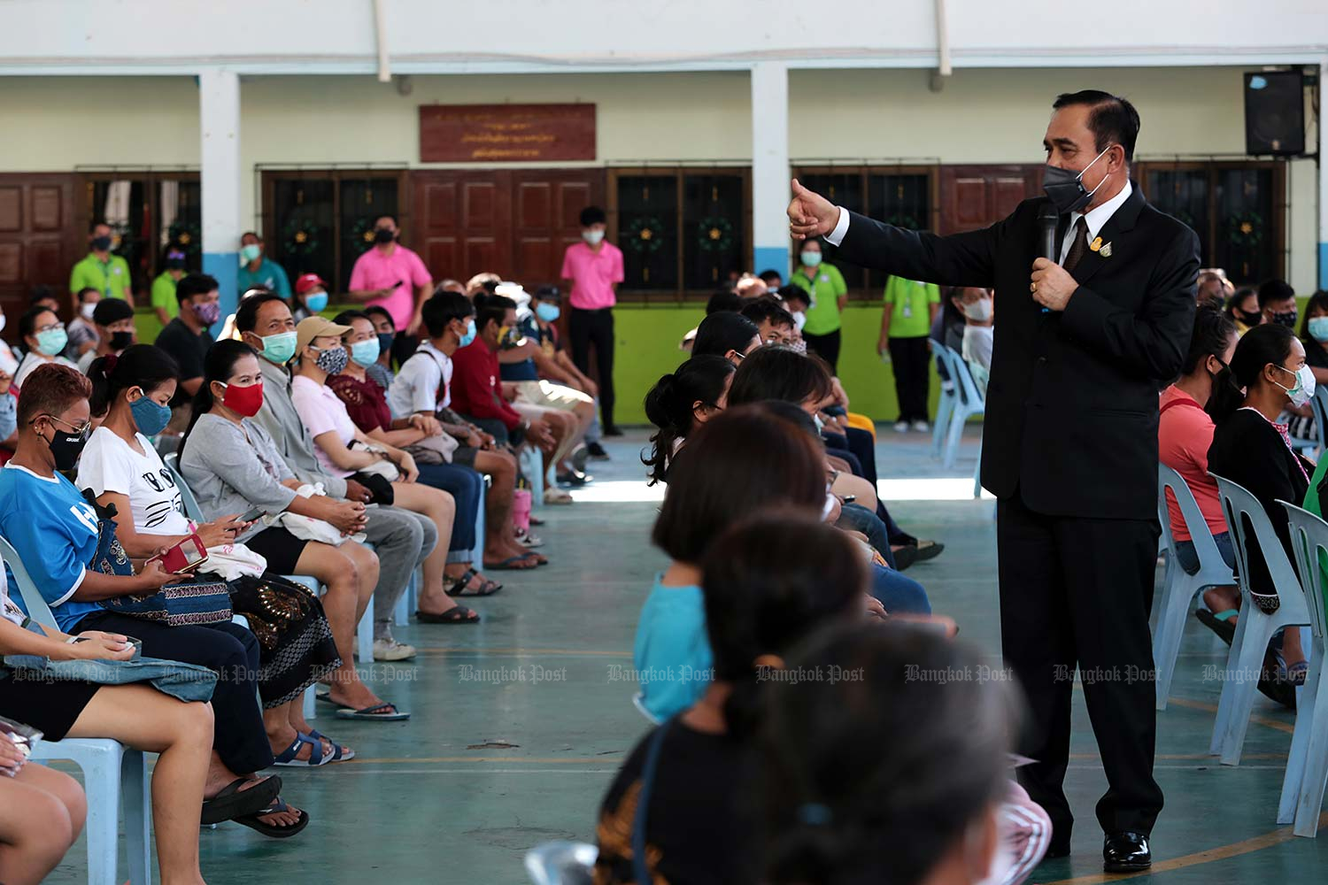 Prime Minister Prayut Chan-o-cha speaks to people at a community centre for distributing food and necessities to people affected by the Covid-19 pandemic at Wat Rakhang Khositaram in Bangkok. The centre was initiated by His Holiness the Supreme Patriarch. (Photo by Chanat Katanyu)