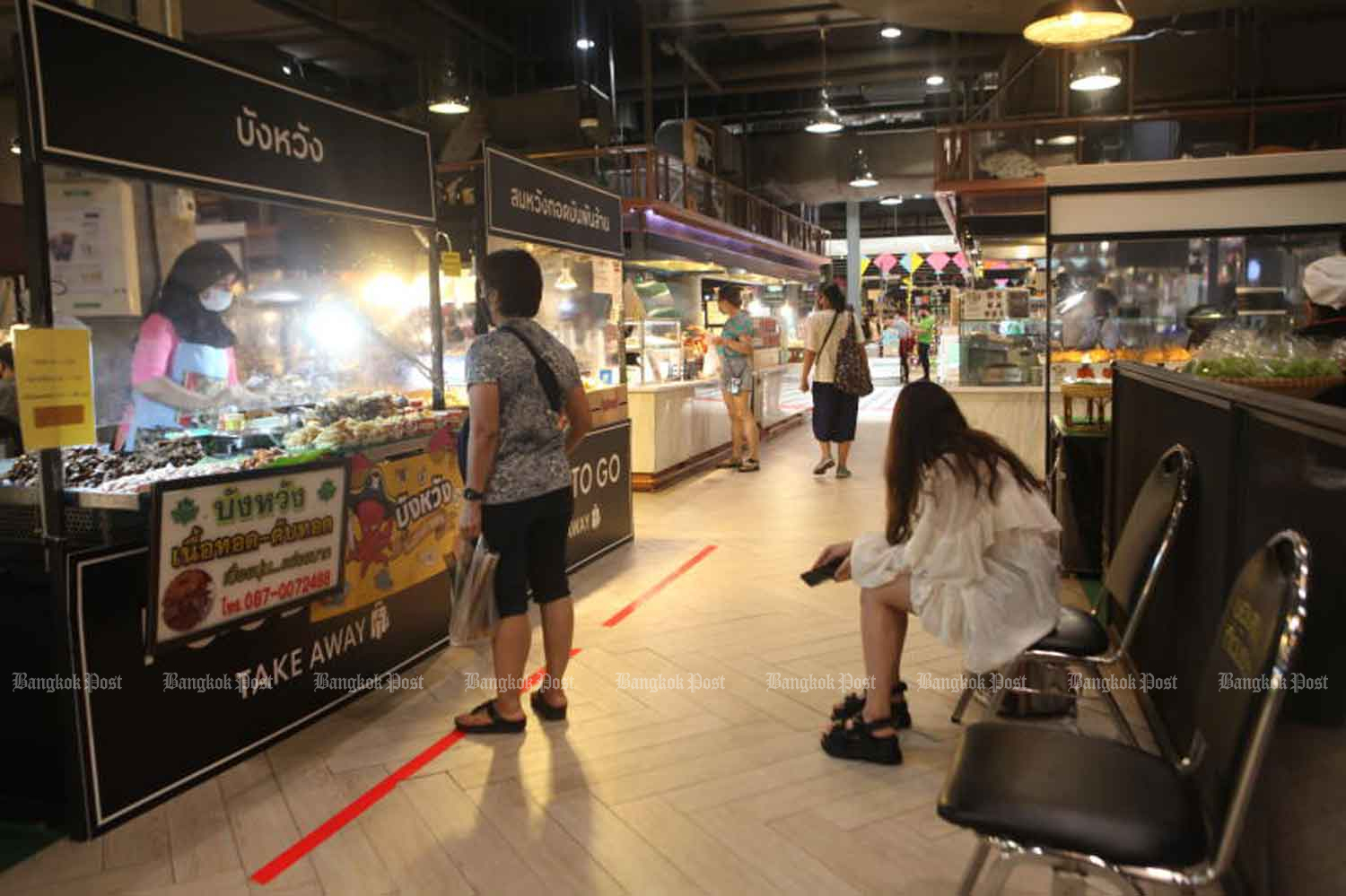 People buy food at CentralFestival EastVille shopping centre in Bangkok on Wednesday. The government will on Friday launch a new phone app to facilitate disease control at shops. (Photo: Arnun Chonmahatrakool)
