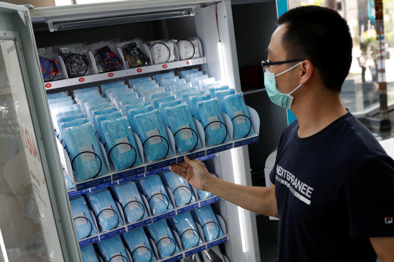 A man fills a vending machine selling protective face masks at a shopping mall that is getting ready to reopen amid the outbreak of the coronavirus disease, in Bangkok on Thursday. (Reuters photo)