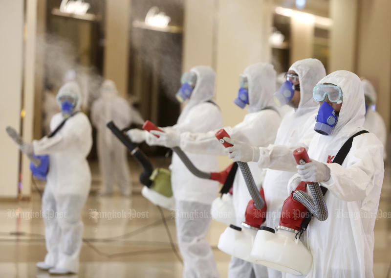 Workers in full protective gear spray disinfectant throughout the interior of Siam Paragon shopping centre on Thursday, ahead of its reopening on Sunday. (Photo: Pattarapong Chatpattarasill)