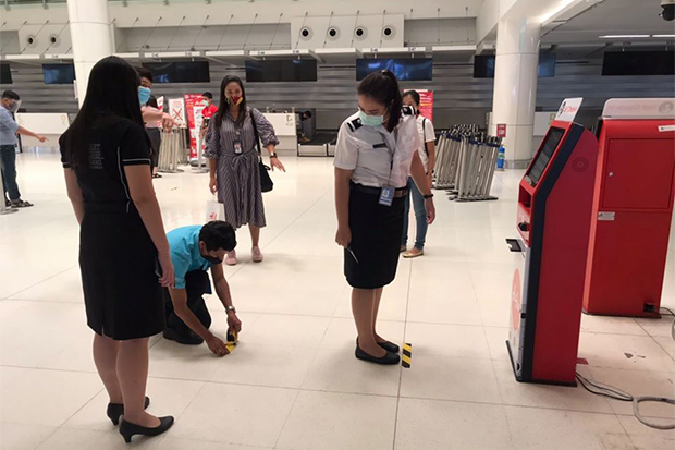 Staff mark safe spots for travellers at Phuket airport on Friday, just a few hours before the plan to resume service on Saturday was suddenly cancelled. (Photo from Phuket airport Facebook account)
