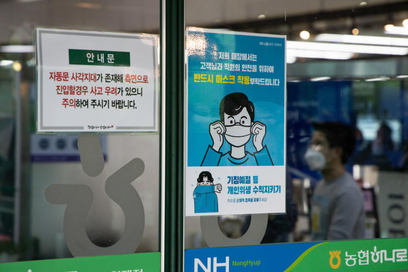 A notice requesting customers to wear protective maks is displayed on the door of a Hanaro Mart supermarket in Seoul on Thursday. (Bloomberg photo)