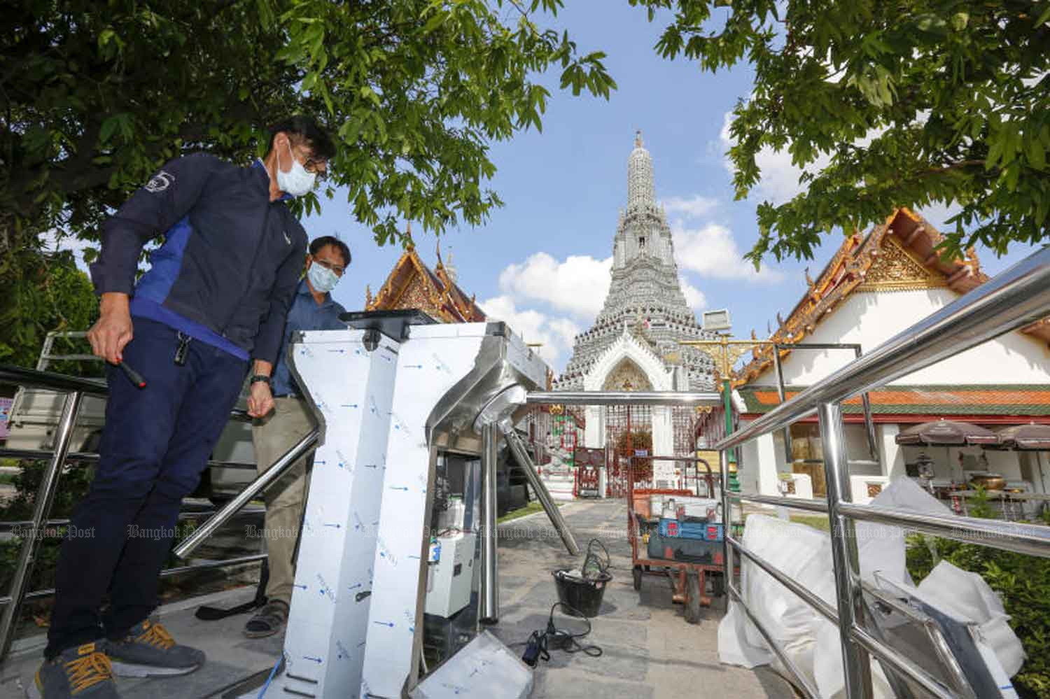 Handymen work on a newly installed turnstile at the entrance to Wat Arun Ratchawararam (Temple of Dawn) in Bangkok ahead of a further easing of the lockdown for business on Sunday. (Photo by Pattarapong Chatpattarasill)