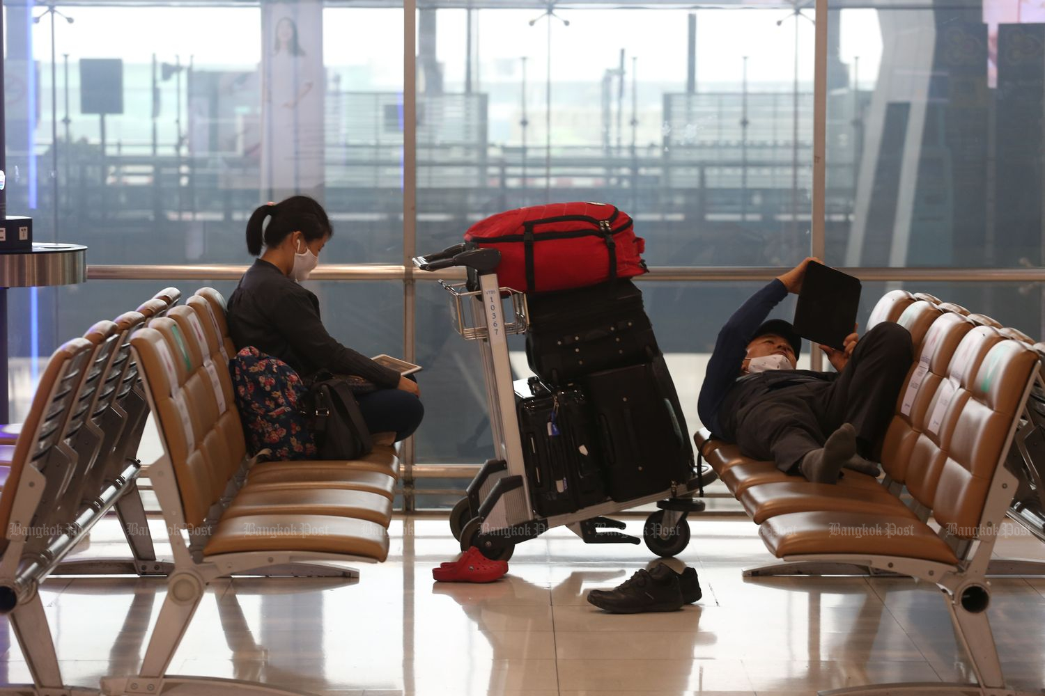 Passengers wait for a flight at Suvarnabhumi airport on Monday. (Photo by Varuth Hirunyatheb)