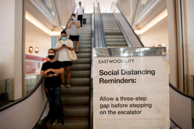A poster reminding shoppers to maintain social distance to prevent the spread of the coronavirus disease is placed beside an escalator in a shopping mall in Quezon City, Metro Manila, Philippines, on Sunday. (Reuters photo)