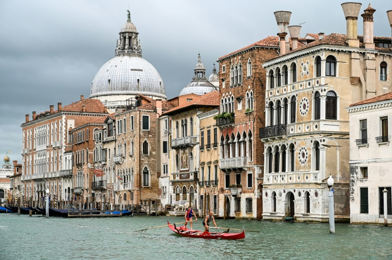 Gondoliers in Venice practise on the Grand Canal as they wait for tourists to return to the city.