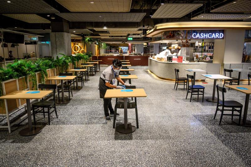 An employee wearing a face mask under a protective face shield cleans tables at the food court of a partially closed shopping mall on May 11, 2020. (AFP photo)