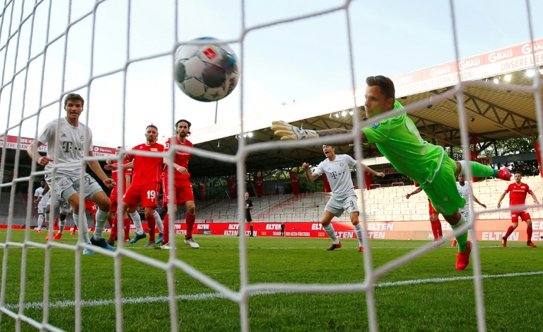 Bayern Munich's French defender Benjamin Pavard (hidden) scores their second goal against FC Union Berlin during the first weekend of Bundesliga play after a two-month absence due to the novel coronavirus pandemic.