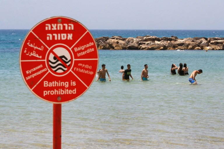 People cool off in the water despite a warning sign prohibiting bathing along the Mediterranean off Israel's coastal city of Netanya
