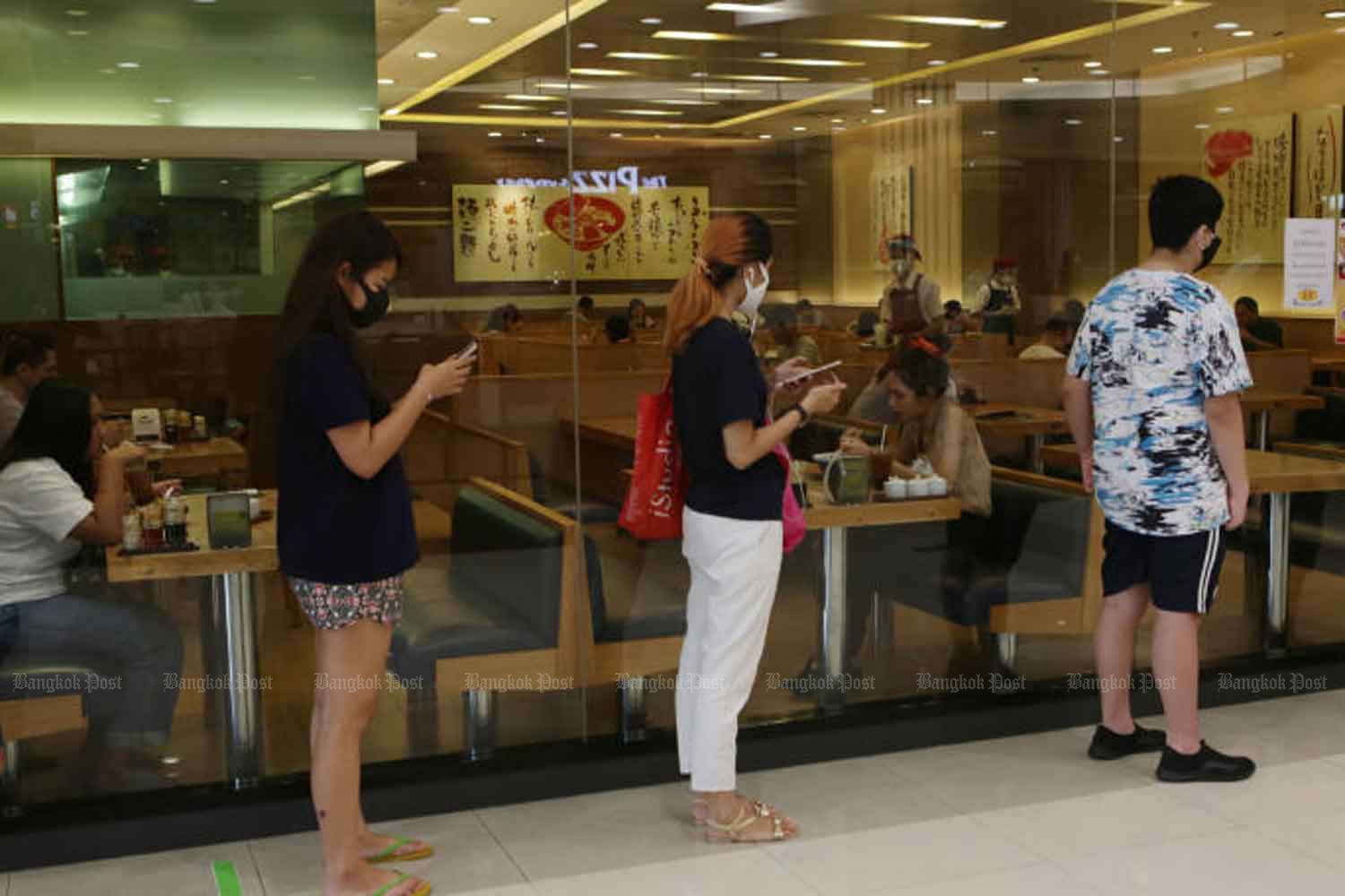 People queue up in front of a restaurant at a shopping mall in Pathum Thani province on Sunday. (Photo: Apichit Jinakul)