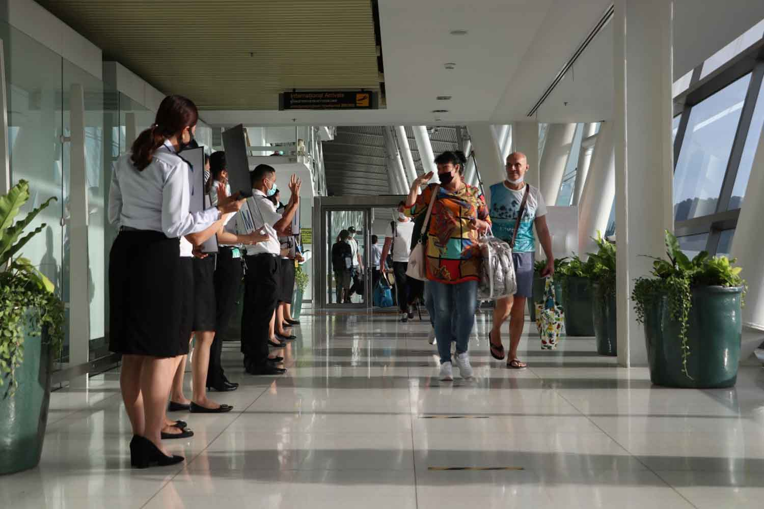 Phuket airport staff stand in line to bid farewell to 235 Russian tourists who left Thailand on a special flight on Monday evening. (Photo: Achadtaya Chuenniran)