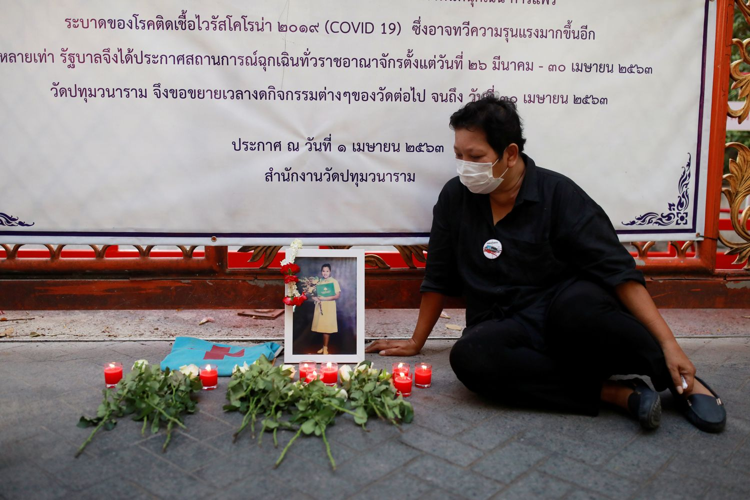 Payao Akkahad, whose daughter Kamonkade Akkahad was shot dead along with five other paramedics at Bangkok's Prathum Wanaram temple, sits near a photo of her daughter at the locked temple's gates in Bangkok on Tuesday. (Reuters photo)
