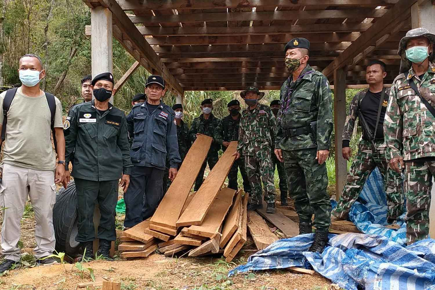 A combined military-police team with some of the teak seized at a house inside Mae Sot National Park in Tak on Tuesday. (Photo: Assawin Pinitwong)