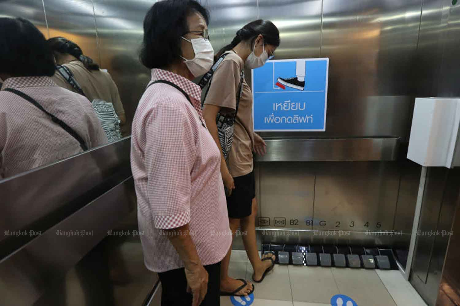 The new norm: A visitor to Seacon Square shopping centre in Bangkok uses foot pedals to activate an elevator, installed so people can avoid touching buttons their fingers, as a disease control measure. (Photo by Wichan Charoenkiatpakul)