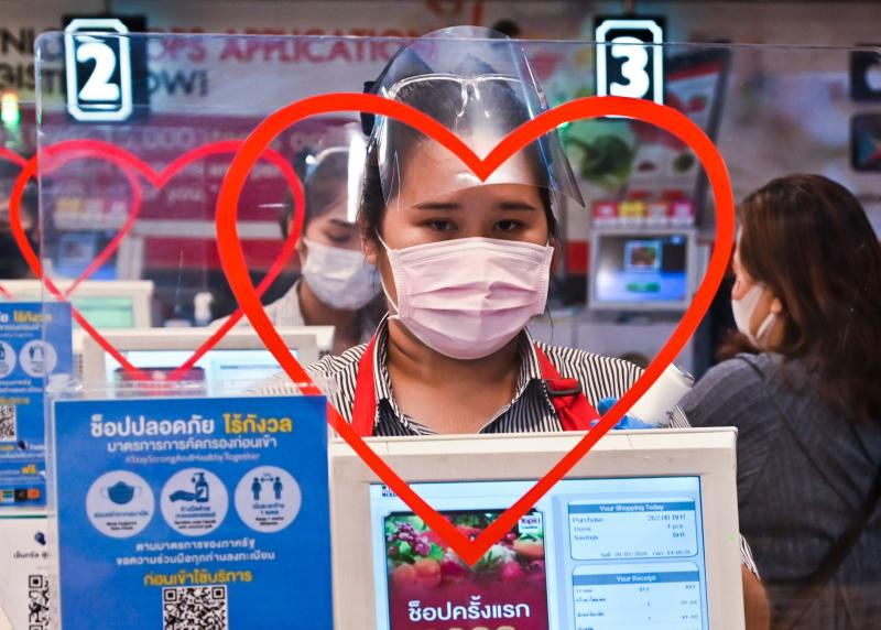 Cashiers wear face masks as a preventive measure against the Covid-19 coronavirus at a supermarket in Bangkok on Wednesday. (AFP photo)