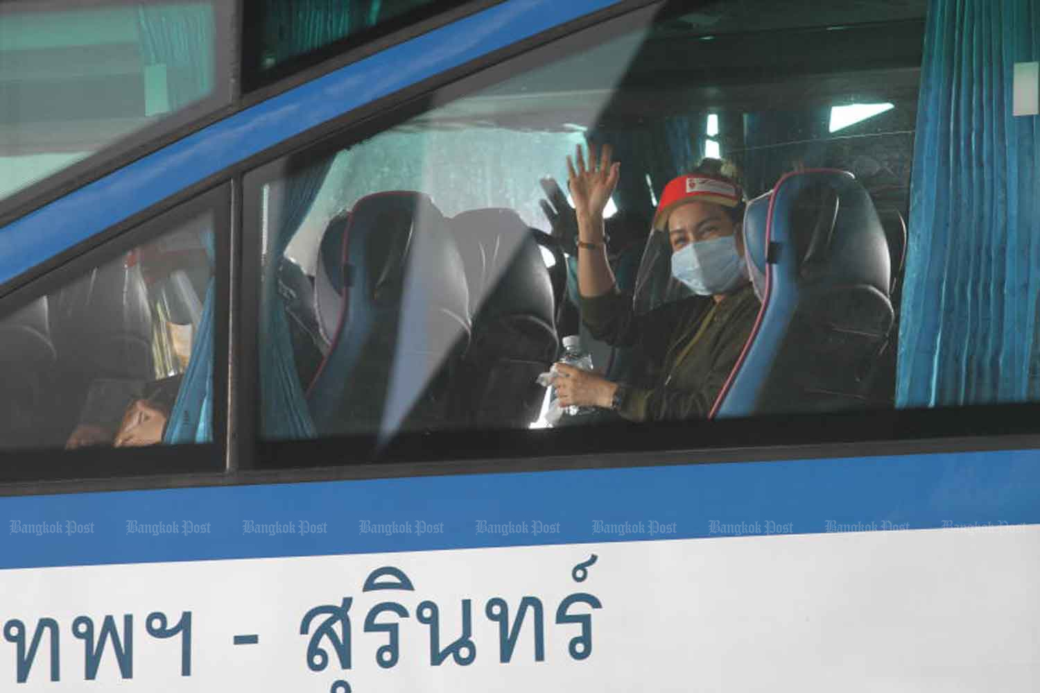 A Thai returnee from India waves to photographers at Suvanabhumi airport before being taken to 14-day quarantine at premises in Samut Prakan province on Thursday. (Photo: Nutthawat Wicheanbut)