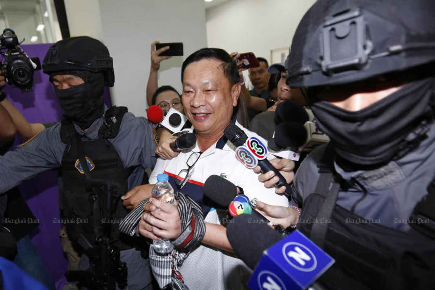 Former deputy commerce minister Banyin Tangpakorn in police custody after being arrested for the murder of the judge's brother in February. (Photo: Pattarapong Chatpattarasill)
