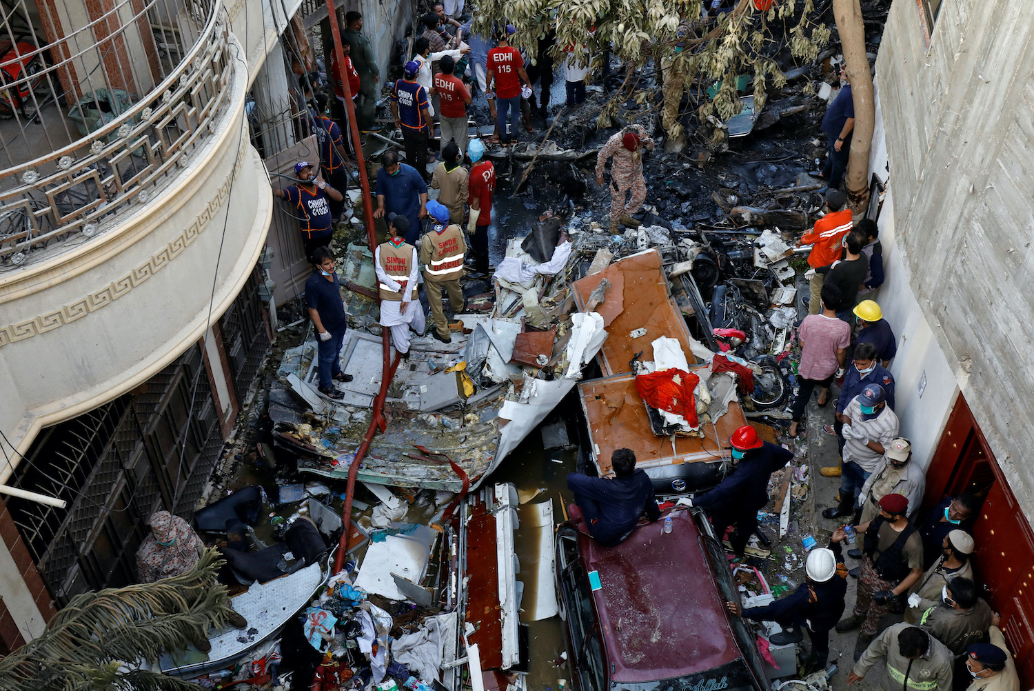 Rescue workers survey the wreckage of a passenger plane strewn along a residential street not far from the airport in Karachi, Pakistan on Friday. (Reuters Photo)