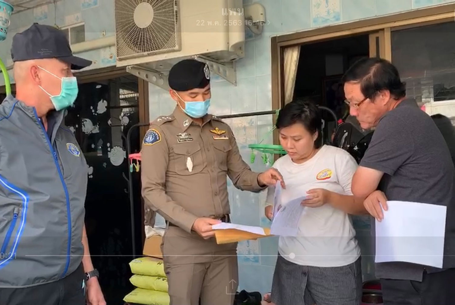 A police officer shows the arrest warrant to a woman accused of allegedly forcing her toddler to swallow bleach to make him look sick for an online advertisement selling her products. (Crime Suppression Division photo)