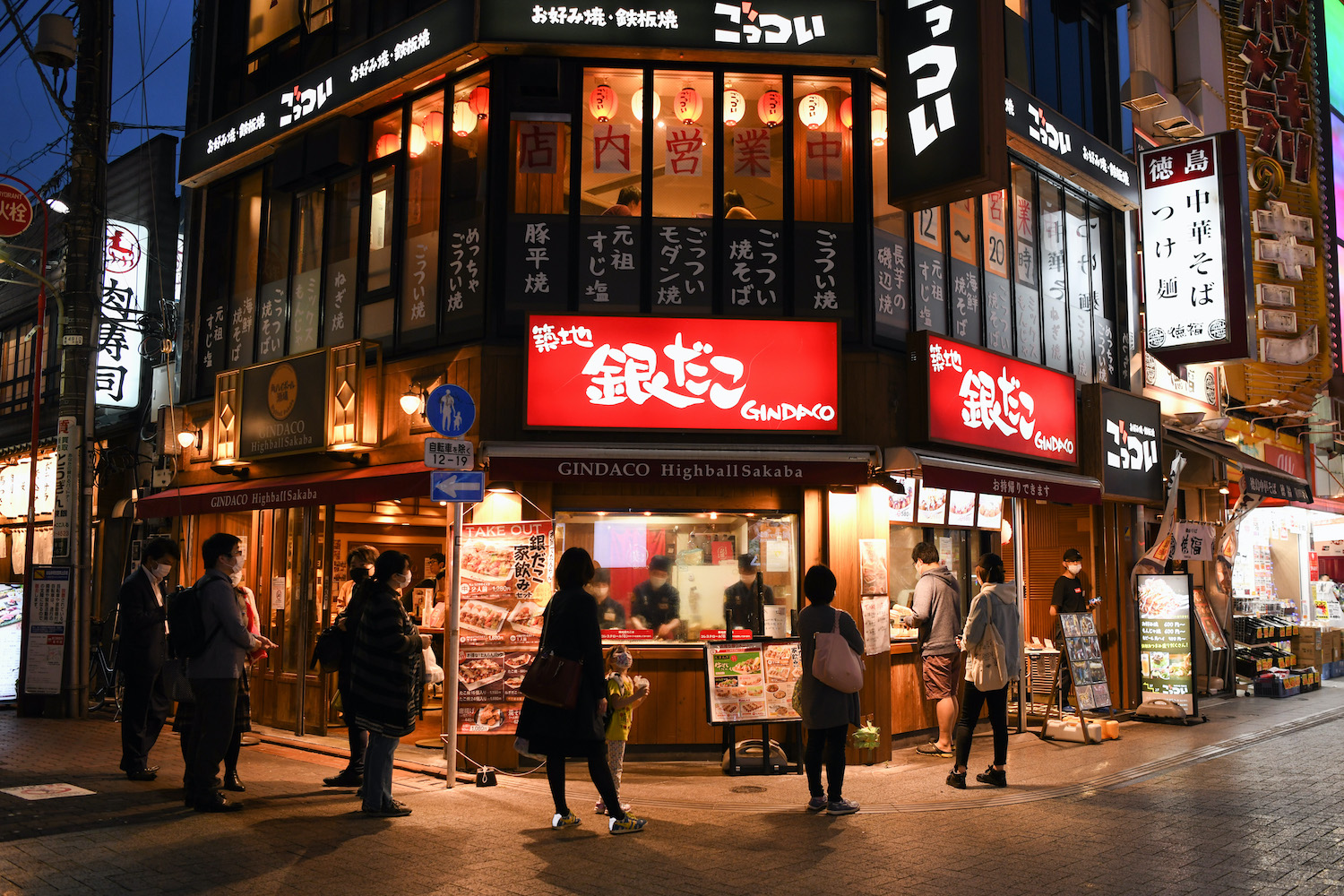 Customers keep their distance while waiting outside a restaurant to order food in the Kamata district of Tokyo on Friday evening. (Bloomberg Photo)