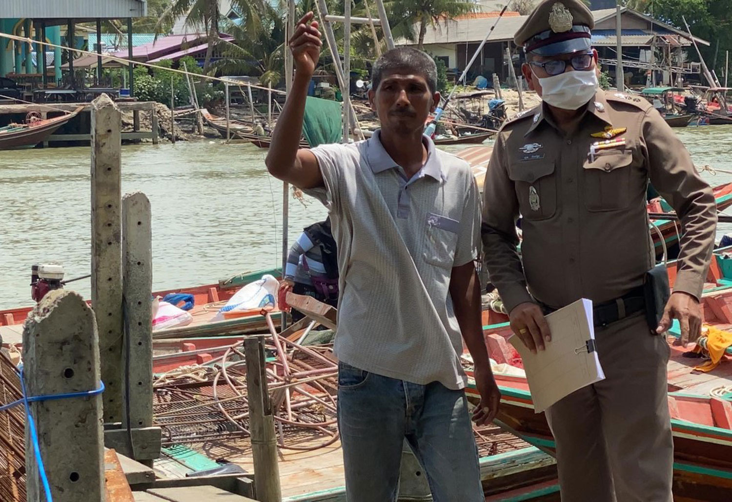 Anucha Binmusa, 46, takes a police investigator to the site where he purchased baby cockles from local fishermen in Surat Thani before three police officers allegedly tried to extort money from him. (Photo: Supapong Chaolan)