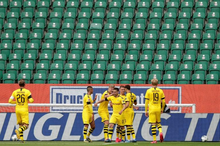 Raphael Guerreiro (C) celebrates scoring the opening goal in Borussia Dortmund's 2-0 win at Wolfsburg in a near-empty stadium.